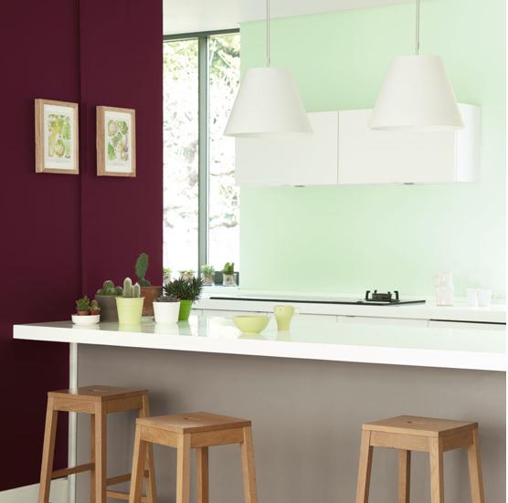 Ambiance naturelle et contraste vivifiant dans la cuisine lorsqu'un mur prune juxtapose un mur vert d'eau. Peintures Vert d'eau, argile grise et choco noisette. Peinture Cuisine & Bains Dulux Valentine