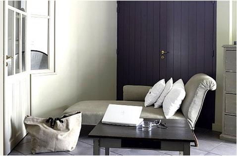 Une déco de petit salon qui renforce la douceur du gris dominant sur le murs et la méridienne avec une touche de couleur violet utilisée pour peindre la porte.