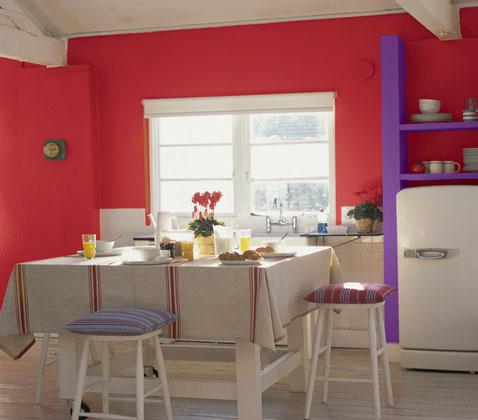pour une decoration de cuisine ambiance flashy peinture murale rouge cramoisi, etagère en bois peint en violet, coussin assorti sur tabouret de table