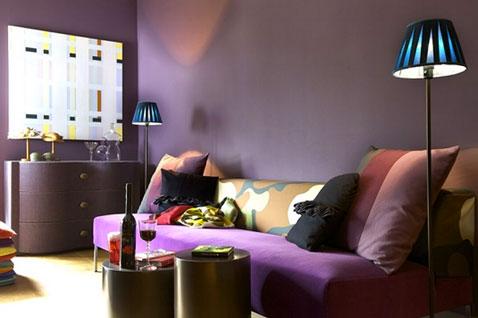Pour une déco chic dans le salon, la couleur violet est mise à l'honneur avec une peinture couleur prune associée à une teinte figue, un canapé violet et coussins noirs