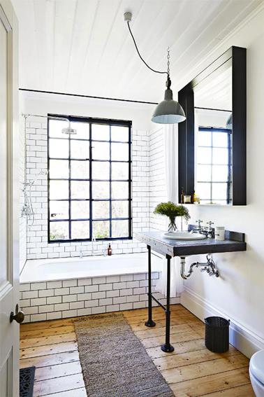 Ambiance rétro pour la déco d'une salle de bain blanc et noir. Mur et tablier baignoire en carrelage blanc et joints gris. Plan vasque noir et sol parquet