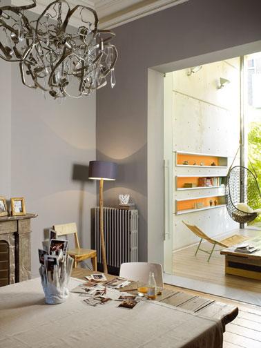 Salle à manger ouverte sur le salon  déclinée dans une harmonie de gris, orange et de bois naturel