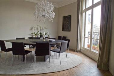 Salle à manger aux lignes épurées et couleurs naturelles. Couleur peinture murale dans deux tons de gris taupe, rideaux gris plus soutenu, grand tapis rond gris perle, table et chaises noires.