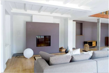 Dans ce salon gris et design, la cheminée encadrée d'un panneau reprenant le gris soutenu du mur du fond, fait face à un canapé d'un gris pastel. Le blanc des coussins et de la lampe boule complète cette harmonie de tons neutres