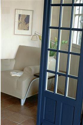 Une déco de salon gris et blanc travaillée en contraste avec une peinture murale en gris blanc, un fauteuil dans un doux ton de gris mastic. Le bleu intense de la peinture de la porte crée un joli contraste