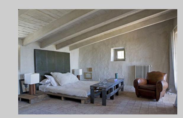 Lit fait avec palette en bois dans une chambre esprit loft. Chevets et pied de lit également fabriqués en palette de bois.