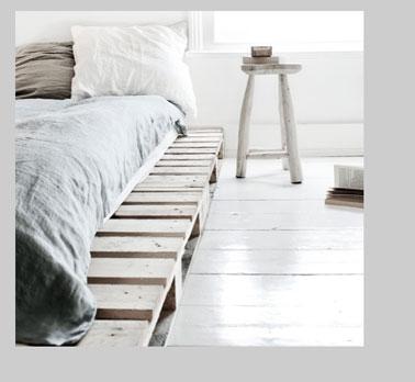 Dans une chambre zen grise et blanche, les palettes du lit sont lasurées en gris clair et posées directement sur le parquet