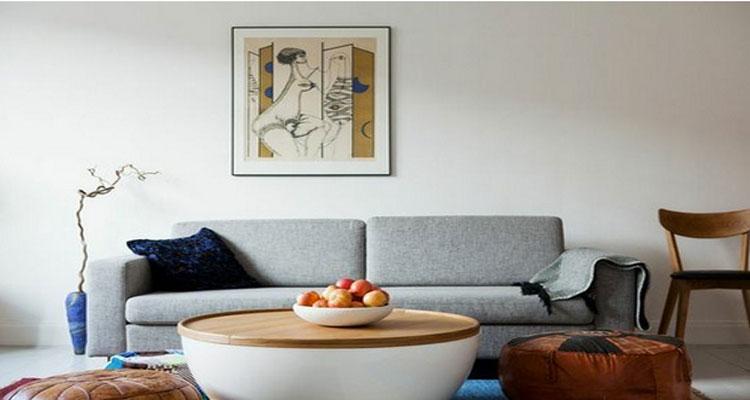 Décoration d'un salon tendance scandinave, mobilier chêne clair, canapé gris pastel, coussins tissus motifs de couleurs avec une table basse design ronde blanche et plateau bois