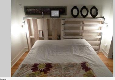 Lit chambre adulte fait avec des palettes bois. La tête de lit également en palette permet des rangements et sert d'étagère pour présenter des cadres photos