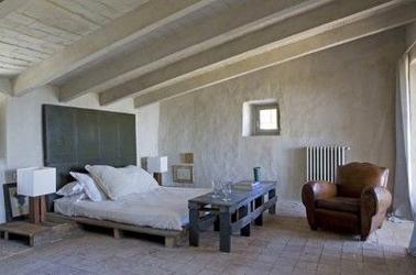 Dans cette chambre, pour compléter le lit en palette bois, la console de pied de lit et la table de chevet sont aussi fabriquées avec des palettes. Pour le chevet, la palette est recouverte d'une planche de bois pour une meilleure stabilité de la lampe sur pied.