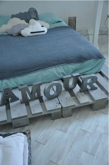 Une chambre d'ado bleu et vert clair qui affiche son slogan love sur un lit en palettes passées à la lasser gris bleu pour créer une harmonie avec la couleurs des murs et du sol de la chambre.