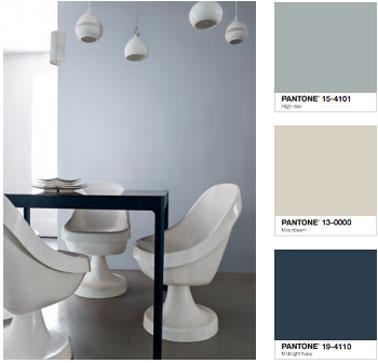 déco Salle à manger design avec une peinture murale gris clair associée au gris béton du sol. Table peinte couleur noir, chaises blanches