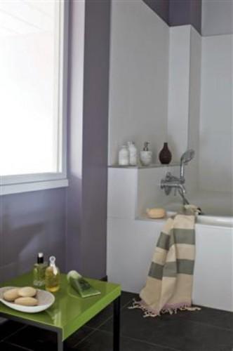 Dans cette petite salle de bain, une peinture couleur parme dynamise le blanc du carrelage et la petite table est repeinte en vert avocat pour apporter un contrat  tonique