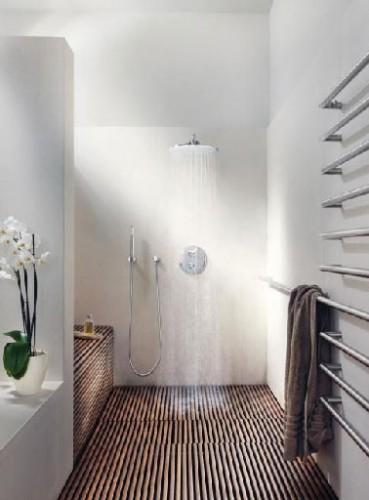 Reproduire dans sa salle de bainl'ambiance d'un spa c'est possible : Un receveur douche italienne XXL installé dans un espace ouvert sur le reste de la salle de bain aux murs blanc immaculé, un sol en teck façon caillebotis, un éclairage travaillé en indirect avec des spots encastrés, un pommeau de douche et une robinetterie Grohe conjuguant technologie et design, et prendre sa douche en version italienne commence.
