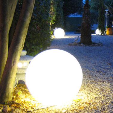 Eclairage d'une allée de jardin avec des luminaires boules posées au sol pour une ambiance mas provencal