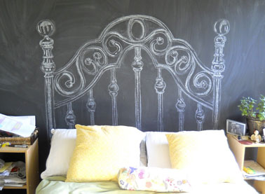 Une tête de lit dessinée à la craie sur le mur facile à fabriquer pour qui a un bon coup de crayon. Toute la surface du mur est peinte avec une peinture à tableau noir. Pour donner l'effet tableau d'école essuyé, frottez à la craie blanche  l'ensemble du mur. La tête de lit est ensuite dessinée à la craie.