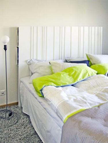 Une tête de lit en médium qui intègre des rangements fabriquée sur le modèle bien connu d'Ikéa. Le panneau de médium repose sur deux rangées de casiers fixés au mur. Les casiers de rangement se trouvent pour un prix modique