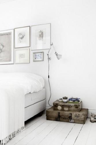Pour la décoration de cette chambre blanche au design épuré, la tête de lit est réalisée avec une composition de dessins au fusain mis sous cadre de plusieurs dimensions pour donner plus de rythme à la composition.