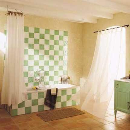 Peindre le carrelage blanc de la salle de bain avec une peinture verte en damier pour lui donner un nouveau look. Avec la même démarche repeindre un meuble en bois avec la même peinture verte jade.