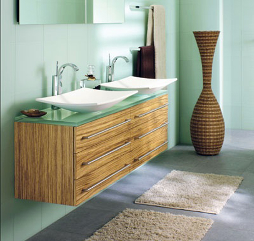 Des couleurs tendres pour une salle de bain nature et zen. Vert d'eau pour le carrelage mural et le plan de travail en verre fumé associé à un meuble lavabo chêne clair. Deux vasques couleur ivoire pour rester dans la même gamme de tons.