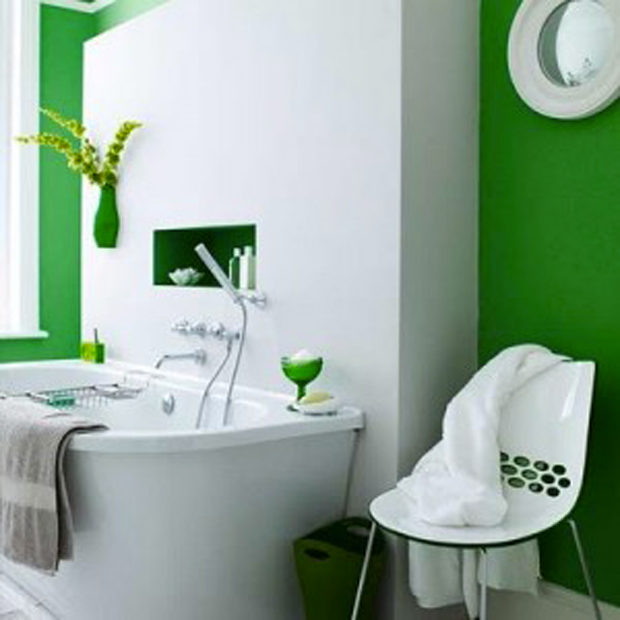 salle de bain verte et blanche pour une ambiance naturelle et design. Ici, c'est le vert émeraude qui est mis à l'honneur sur les murs. La chaise et les accessoires de salle de bains reprennent le vert émeraude de la peinture pour un bel équilibre des valeurs