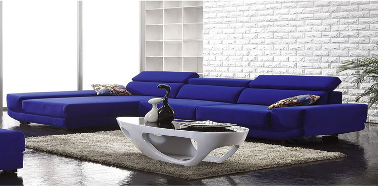 En bleu et blanc le design s'invite dans le salon. Le canapé bleu roi constitue l'élément fort du salon autour des matériaux bruts des murs en brique blanche et du sol béton peint en noir
