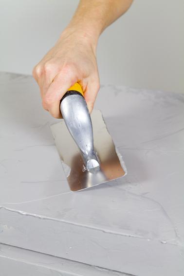 Appliquer le béton ciré en couche épaisse sur le meuble à l'aide d'une taloche en inox. Temps de séchage : 4 heures