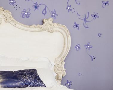 Déco chambre violet avec une  de ses nuances claires pour la peinture murale parme de Dulux Valentine et des fleurs violet plus soutenu en décoration murale autour de la tête de lit blanc ivoire