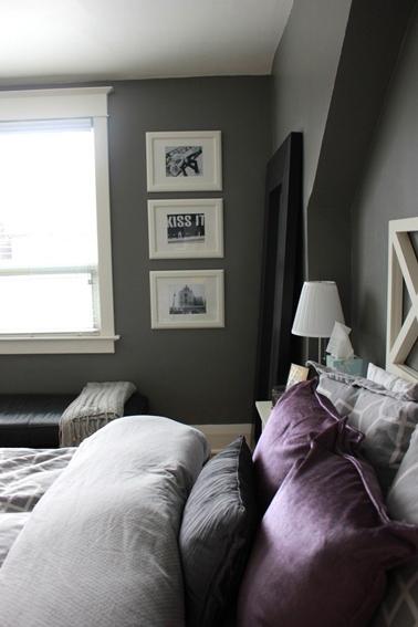 Du violet pour la déco de la chambre introduit en touches avec les coussins de lit autour d'une harmonie de gris et blanc pour les murs et les éléments de décoration