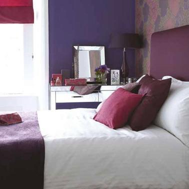 Déclinaison de violets pour la déco de la chambre avec peinture mur et tête de lit violet, un autre mur vieux rose linge de lit blanc recouvert de plaid et coussins nuances de violet