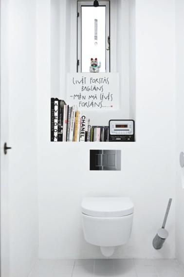 Peinture WC couleur blanc relevée de touches de noir avec les éléments déco, une décoration wc facile à réaliser en blanc et noir. Cuvette wc et murs blanc. Le rebord de la fenêtre est transformé en petite bibliothéque pour accueillir quelques livres aux couvertures noires et blanches