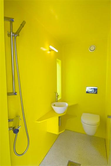 Déco WC design avec autour de la cuvette wc suspendu et du lave main blanc une peinture jaune citron sur les murs et le plafond