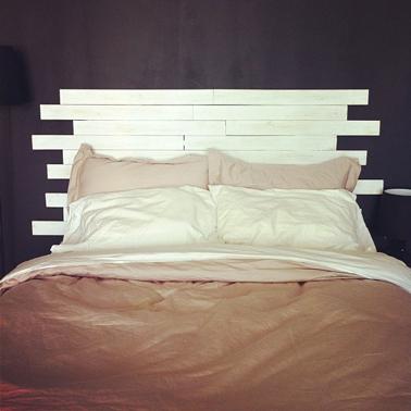 Une tête de lit en bois hyper sympa à faire avec des lames de parquet de récup. Le coté sympa est apporté avec les lames de bois longueurs inégales et le contraste couleur entre le mur noir et la tête de lit peinte couleur ivoire