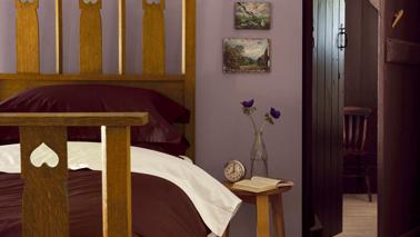 Ambiance cocooning dans la chambre avec des murs d'un doux  violet mat  mis en valeur avec une peinture prune pour les boiseries