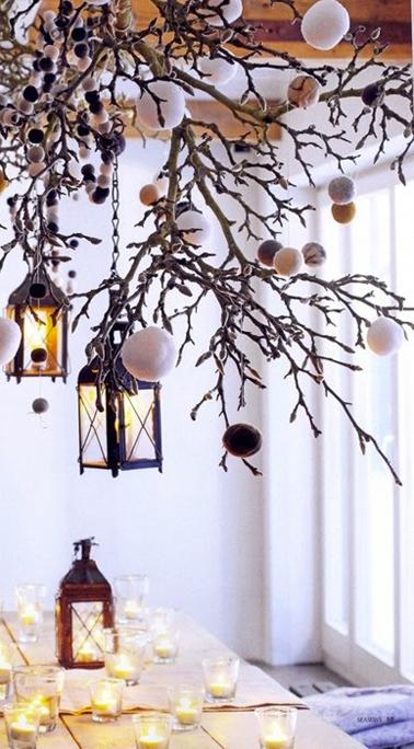 Pour un décor de Noël original au dessus de la table,  une suspension faite de branchages et de guirlande de pompons à accrocher au dessus de la table de Noël