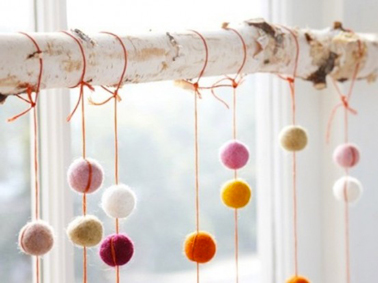 Pour une déco de Noël originale et pas chère, voici une guirlande de Noël réalisée avec des pompons de laine de couleurs et suspendus à une branche d'arbre blanchie