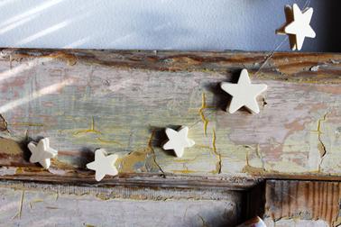 Une guirlande déco de Noël à faire soi-même avec quelques étoiles en bois ou de carton, du fil de nylon et un pistolet à colle