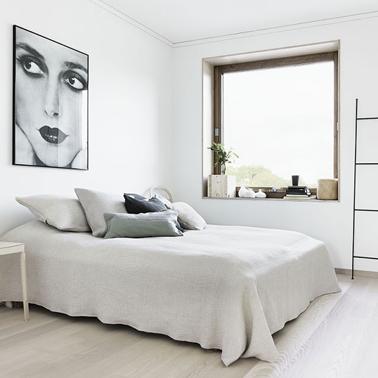 Déco d'une chambre zen et minimaliste dans une douce harmonie de blanc et gris. Sol en parquet de bois blanchi, dessus de lit blanc cassé et coussins de lit dans un dégradé de tons blanc et gris clair. Au mur un poster en noir et blanc apporte une note de fantaisie.