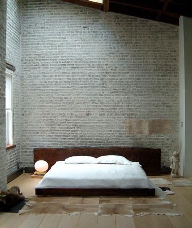 Déco chambre zen avec mur en pierre de parement gris et grand lit sur estrade. La tête de lit en bois foncé apporte un note confortable et chaleureuse.