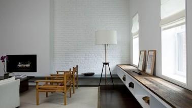 Magnifique salon design ou le bois des quelques meubles et du parquet wengé créent une ambiance cocooning autour des murs d'un blanc immaculé.