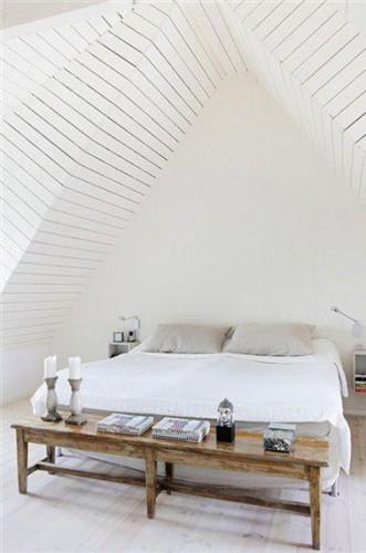 Dans cette chambre aménagée sous les toits, l'architecture du plafond en lambris peint en blanc est l'élément déco mis en avant. Petit clin d'oeil à une ambiance zen, le bouda placé sur la console en bois au pied du lit