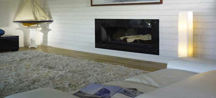 Dans un salon moderne, un lambris bois aspect brossé blanc sur les murs pour une ambiance cosy autour de la cheminée et du parquet bois.