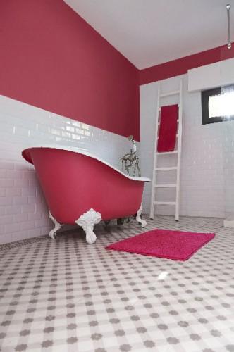 Lorsquela couleur de peinture sert à redonner vie à une salle de bain dont on veut conserver le charme de l'ancien, c'est efficace ! Ici c'est un Bougainvillier, une teinte de rose du nuancier Zolpan qui dynamise la faïence murale d'un blanc éclatant. Profitant de l'occasion, la baignoire îlot enveloppe l'extérieur de sa coque de la même couleur intense.