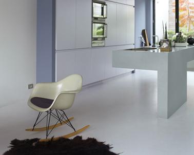 Harmonie de couleurs pastel pour une cuisine ouverte sur le salon : Murs peinture couleur gris embruns et bleu acier, le sol en béton gris perle renforce l'ambiance minimaliste de la cuisine et les touches de chocolat ajoute une impression de confort tranquille. Peinture Dulux Valentine