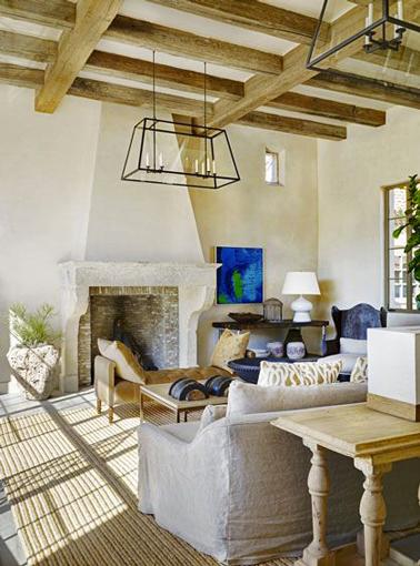 Dans le salon d'une maison de campagne la douceur de la couleur lin de la peinture des murs et du plafond trouve un écho avec la couleur des fauteuils en toile de lin et permet d'introduire des touches de bleu vif pour une déco éclectique
