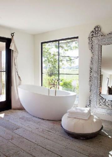 Une ambiance de salle zen construite autour du blanc et du gris perle. Sur les murs une peinture dans une nuance blanc cassé pour sublimer le blanc pur et les lignes de la baignoire en îlot posé sur un parquet de chêne grisé