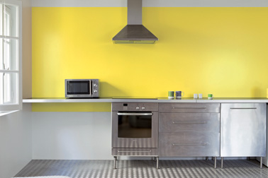 dans la cuisine, un jaune primaire sur le mur de la crédence  s'associe parfaitement aux éléments en aluminium et inox. Tollens Pantone couleur  Buttercup