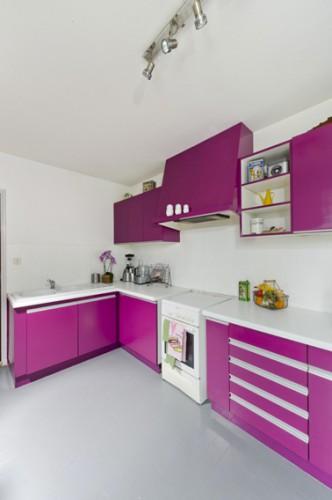 Pour repeindre un meuble en bois avec la peinture pour meuble de cuisine GripActiv V33 sans poncer dans cette cuisine, 2 couches de peinture couleur violet (Papillon) sur les meubles haut et bas et couleur blanc sur la crédence en carrelage. Photo après
