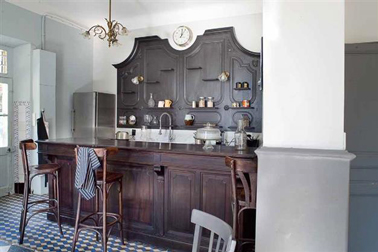 Des nuances de peinture couleur grise pour mettre en valeur les meubles chêne foncé de la cuisine. Photo Tollens