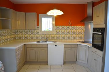 Pour repeindre les meubles de la cuisine rustique c'est la peinture pour meuble de cuisine couleur tourterelle GripActiv V33 qui est choisie pour s'harmoniser avec la couleur du carrelage de la crédence et le rouge de la peinture murale